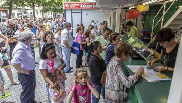 Imagen de un grupo de personas haciendo cola frente al mostrador para hacerse con los primeros boletos de la tómbola.