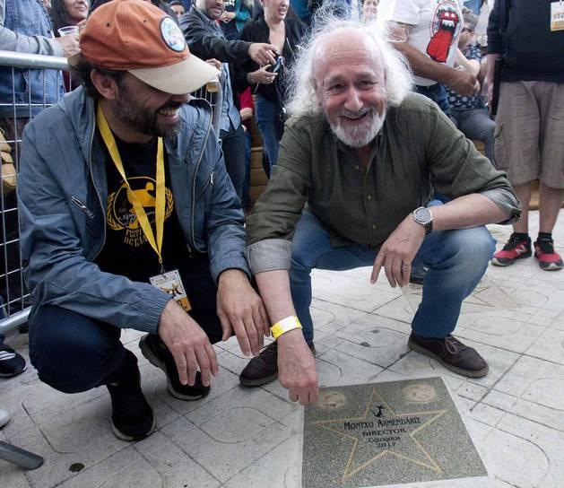 Imagen del director de cine Montxo Armendáriz (derecha) junto a la placa con su nombre en el Festival de Cans, en O Porriño (Pontevedra).