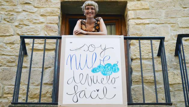 Leire Olkotz, posando en un balcón de Tafalla con el verso de uno de sus poemas en un cartel, como quiere hacer en Pamplona para San Fermín.