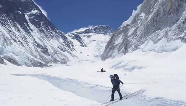 Un montañero cruza una grieta por una escalera en el 'Valle del silencio' con la cima del Lhotse al fondo.