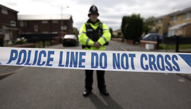 Un policía vigila la entrada a una calle de Manchester.
