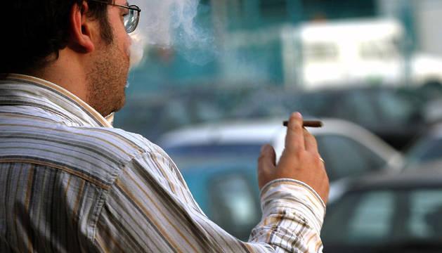 Un trabajador fuma un cigarro en el aparcamiento de una empresa.