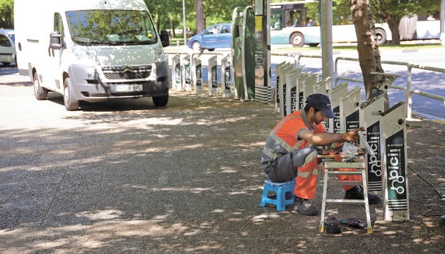 Foto de un operario revisa  el sistema técnico en la base de préstamo de bicicletas de la Avenida del Ejército.