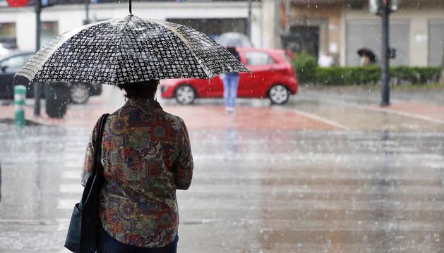 Foto de una mujer se protege con su paraguas en medio de un aguacero primaveral de días pasados.