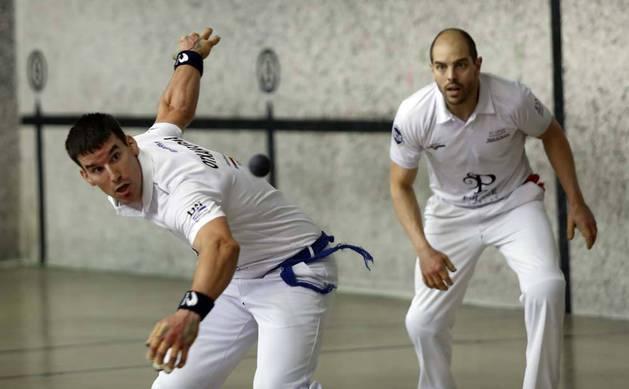Imagen del pelotari Gaizka Otxandorena espera la pelota ante la atenta mirada de Alberto Ongay.