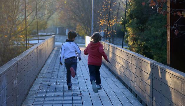 Dos niños juegan en un puente sobre el río Arga, en la zona de Alemanes.