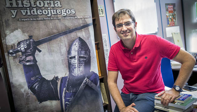 Íñigo Muneta, fotografiado en su despacho de la UPNA al lado del cartel de un congreso dedicado a la historia y los videojuegos.
