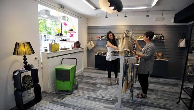 Natalia (izda.) y Ana Álvarez Iriso colocan la tienda con el deshumidificador (izda. de la imagen) secando el suelo.