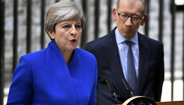 La primera ministra británica, Theresa May (i), ofrece una rueda de prensa junto a su marido, Philip (d), en el número 10 de Downing Street tras reunirse con la reina Isabel II.
