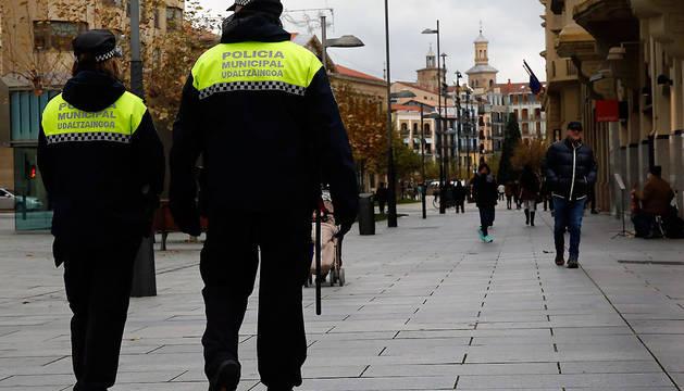 Dos agentes de la Policía Municipal de Pamplona patrullan por la avenida Carlos III.
