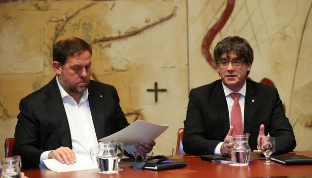 Carles Puigdemont, junto al vicepresidente catalán, Oriol Junqueras, al inicio de la reunión extraordinaria del Consell Executiu