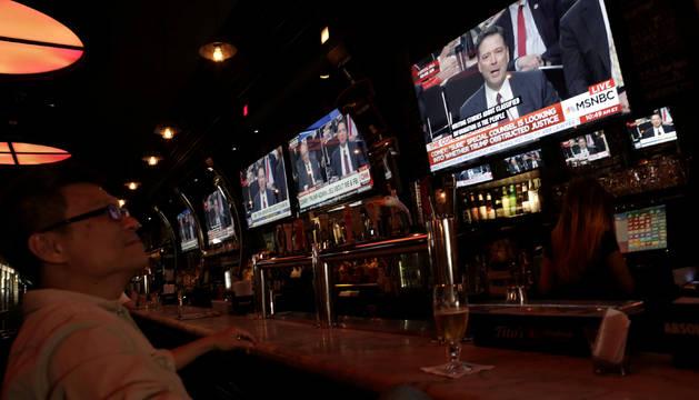 Un hombre ve por TV las declaraciones del exdirector del FBI, James Comey, ante la Comisión de Inteligencia.