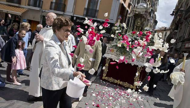 Una mujer lanza pétalos de flores en la procesión del año pasado.