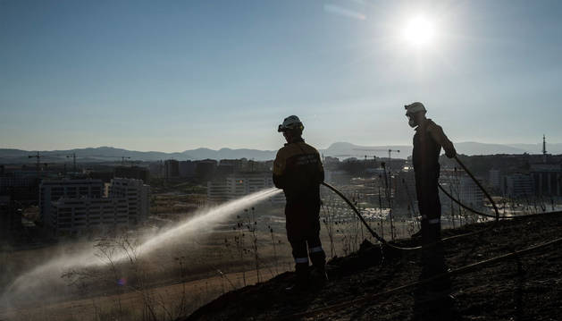 Unos bomberos sofocan un incendio.