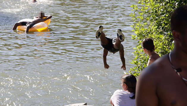 Jóvenes disfrutan del baño en el  río Arga junto a la presa del Club Natación, bajo la mirada de un grupo de menores.