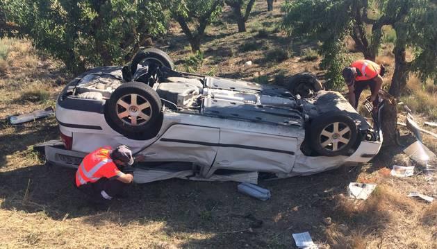 Dos agentes de Policía Foral, junto al vehículo accidentado en Cascante.