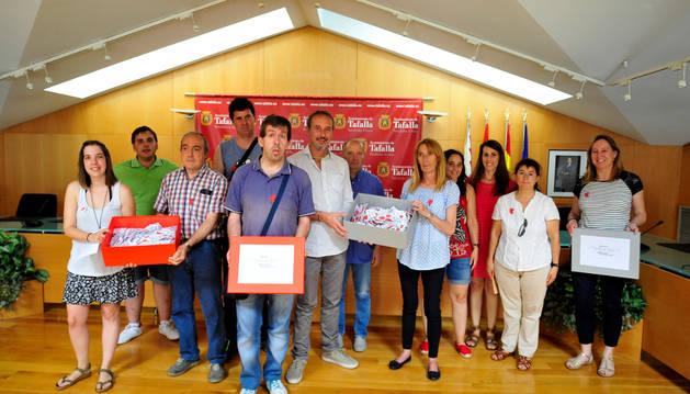 Usuarios del centro Ordoiz entregan las manos que han elaborado a representantes municipales.