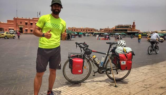 Xabi Luna hace el signo de la victoria en la plaza de Jemma el-Fna en Marrakech, donde terminó su viaje.