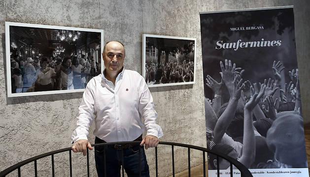 El fotógrafo pamplonés Miguel Bergasa posa junto a varias de sus imágens que forman parte de la exposición 'Sanfermines', en el Palacio Condestable de Pamplona.