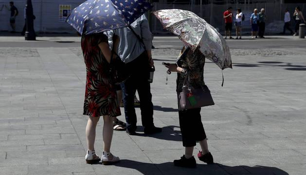 Varias personas con paraguas protegiéndose del sol en la Puerta del Sol de Madrid.