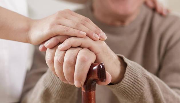 Una cuidadora cuida de una persona mayor.