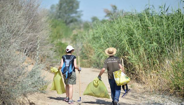 Imagen de dos voluntarios recogiendo basura.
