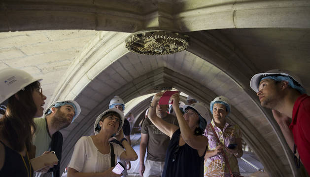 Un grupo de asistentes a la visita guiada del claustro de la Catedral contempla un detalle de la bóveda.