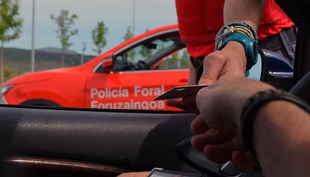 Un conductor entrega su documentación a un agente de la Policía Foral en un control rutinario.