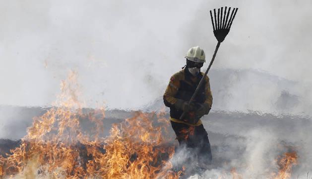Un auxiliar durante las labores de extinción del jueves en Esparza de Galar trabajando con un batefuegos.