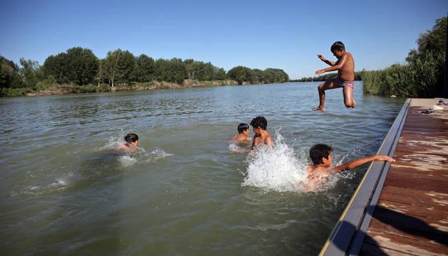Un grupo de niños se refresca en el río Ebro a su paso por Tudela.