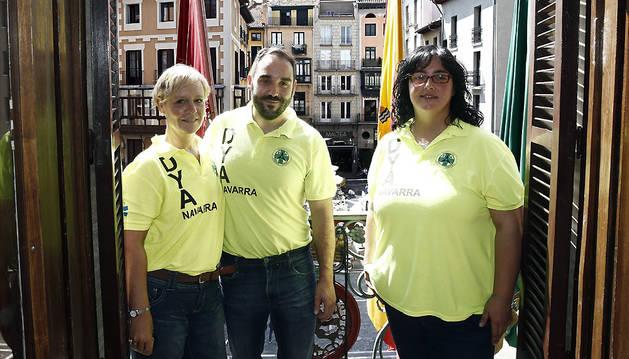 El presidente de DYA en Navarra, Mikel Corres (c), y las voluntarias Mercedes Azcárate (izda.) y María Calado posan en el balcón del Ayuntamiento después de conocerse que la asociación DYA (Detente y Ayuda) ha sido la candidatura elegida en votación popular para tirar el próximo 6 de julio al mediodía el Chupinazo anunciador de los Sanfermines de 2017.
