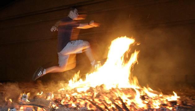 Foto de un joven salta una hoguera en la noche de San Juan.