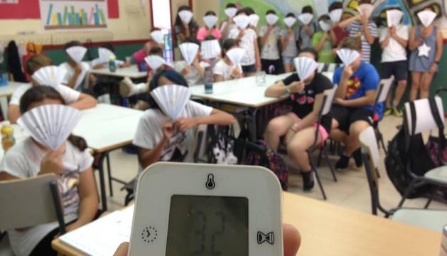 Imagen de los estudiantes con los abanicos y la temperatura en clase
