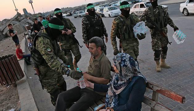 La milicia armada de Hamas reparte agua durante el final del Ramadán