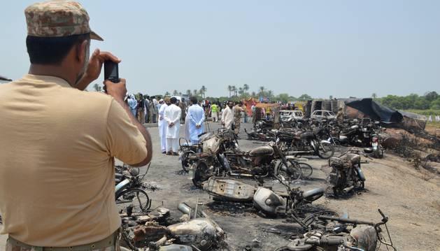 Foto de un policía pakistaní toma fotos en el lugar del suceso.