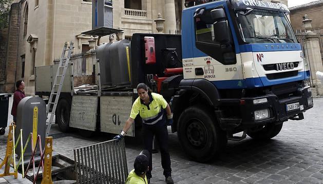 Una grúa pluma retira los buzones de recogida neumática en la calle Navarreria, junto a la Catedral de Pamplona, que serán sustituidos por contenedores de recogida selectiva con capacidad para 1.000 litros, en los que se podrá depositar separadamente la materia orgánica, resto, papel y envases.