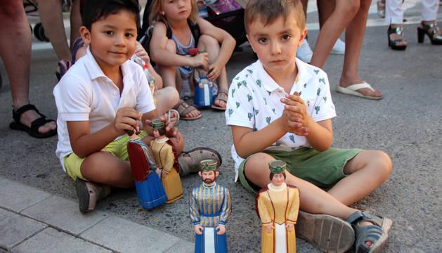 Varios de los asistentes al acto de presentación de los gigantes en miniatura posaron con las figuras originales de la Comparsa de Milagro.