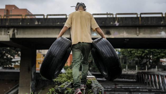 Foto de un simpatizante de la oposición carga llantas para construir una barricada en una protesta en contra de el gobierno de Nicolás Maduro.