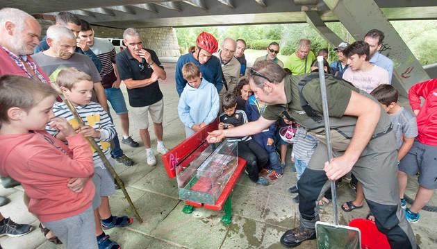 Imagen de José Ardaiz explicando a los asistentes las especies encontradas en el río en el muestreo.