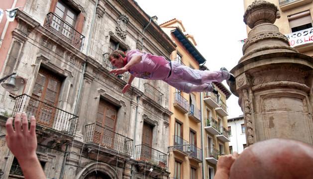 Imagen de un extranjero saltando desde la fuente de Navarrería, práctica prohibida por el Ayuntamiento de Pamplona.