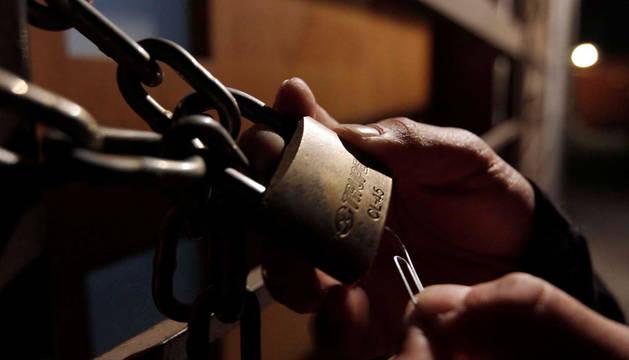 Un ladrón intenta abrir un candado.