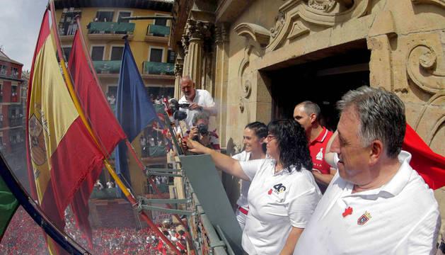 La vicepresidenta de la DYA, María Calado, y una de sus voluntarias más veteranas, Paula Ramirez, junto al alcalde de Pamplona, Joseba Asiron (d), prenden desde el balcón del Ayuntamiento la mecha del Chupinazo.