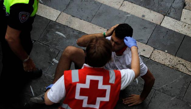 Imagen de un sanitario atiende a un corredor en la plaza Consistorial en el segundo encierro de los Sanfermines.