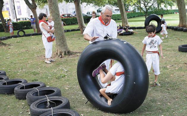 Imagen de abuelo y nieto jugando con los neumáticos de Birjolastu, en Antoniutti.