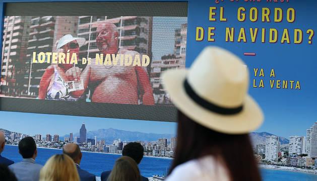 Un grupo de personas observa un spot publicitario de la Campaña de Verano del Sorteo Extraordinario de Navidad 2017.