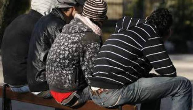 Los jóvenes con dificultades de inserción laboral centran la medida  de los 430 euros. Un grupo de jóvenes, sentados en un banco.