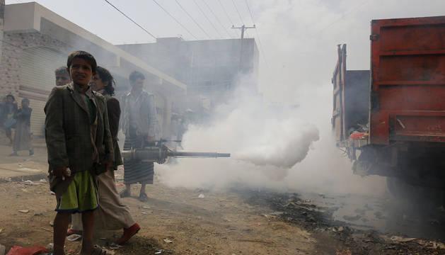 Varios niños junto a un operario que fumiga en Sanaía, en Yemen, ante la epidemia de cólera.
