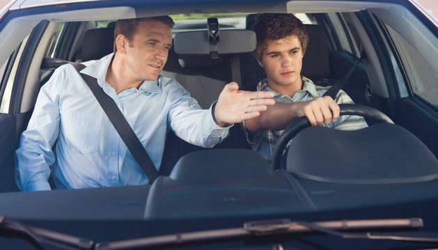Un profesor de autoescuela imparte unas instrucciones a un alumno en el interior del coche.