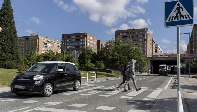 Dos jóvenes cruzan un paso de cebra en la calle Esquiroz. Al fondo, el barrio de Iturrama.