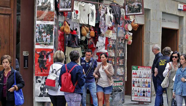 Foto de dos turistas salen del establecimiento Souvenirs Estafeta, ubicado a la altura del número 47 frente al otro comercio de regalos, Olentzero.
